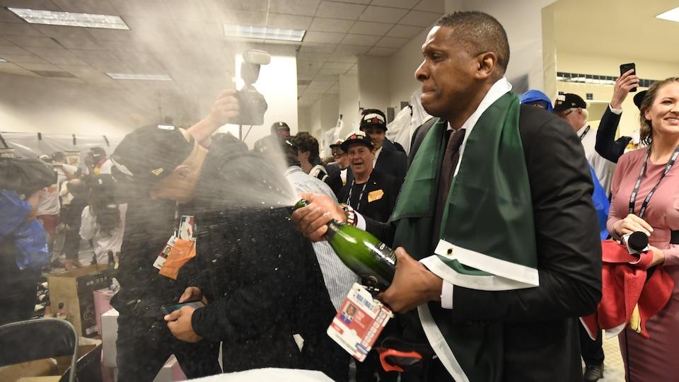 Un homme ouvre une bouteille de champagne.