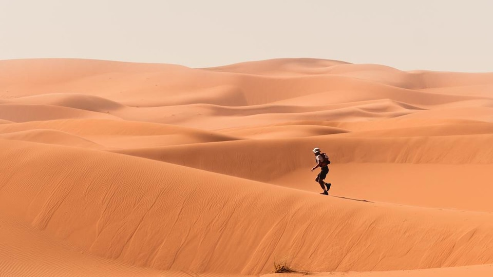 Un homme court dans le désert du Sahara, au Maroc.
