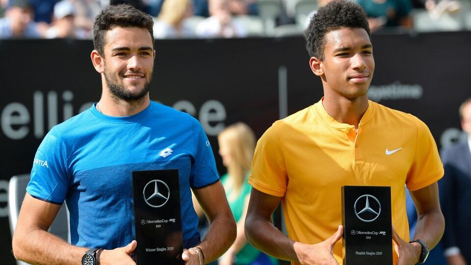 Ils posent avec les trophées de gagnant et de finaliste entre les mains.