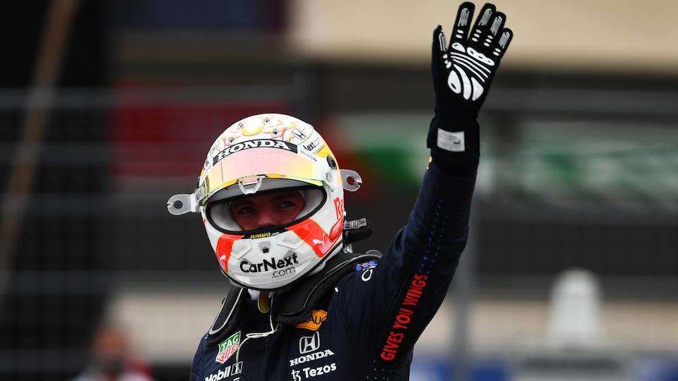 Max Verstappen, casqué, lève le bras gauche.