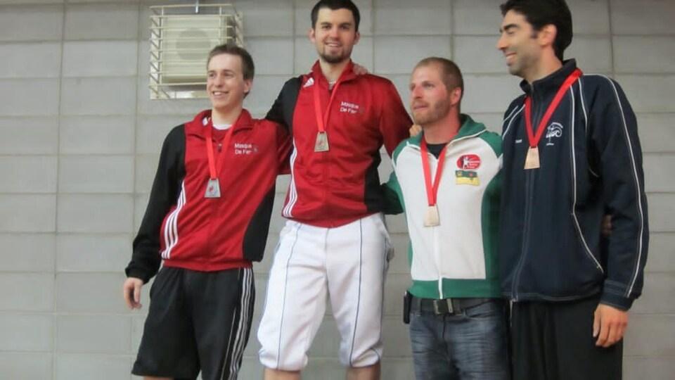 Un athlète, médaille d'or au cou, célèbre sa victoire avec ses deux adversaires après une compétition d'escrime.
