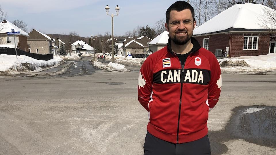 Un athlète prend la pose pour une photo dans les rues d'un quartier résidentiel. Il porte son manteau d'athlète du Canada.