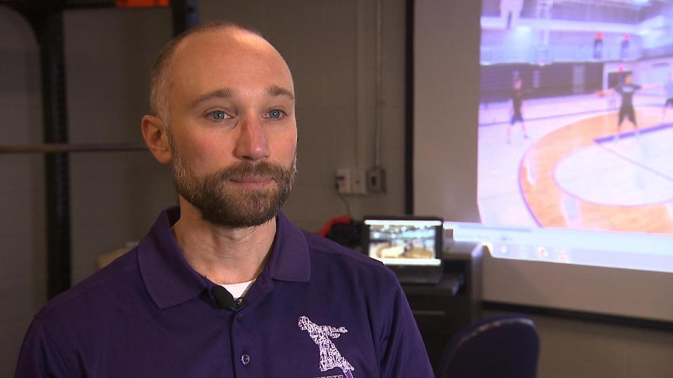 Il accorde une entrevue à un journaliste devant un écran diffusant un entraînement de basketball.