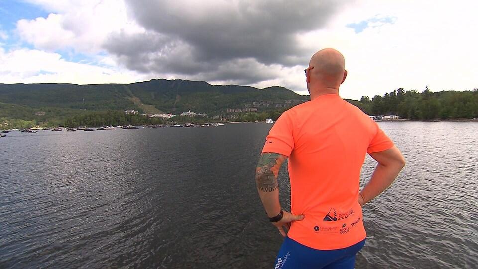On le voit de dos regarder le lac.