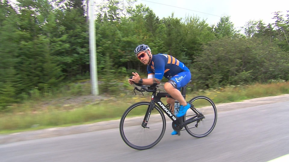 Il est en position aérodynamique sur son vélo.
