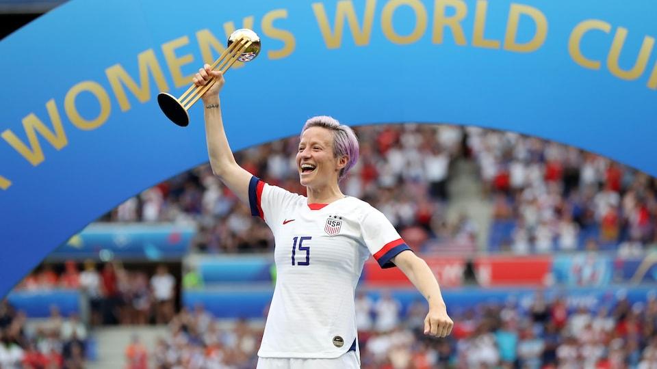 Elle tient le trophée de la Coupe du monde dans sa main droite.