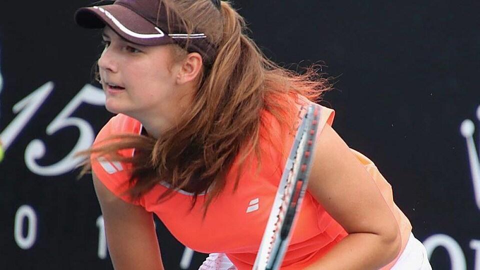 Une joueuse de tennis attend le retour de balle de son adversaire lors d'un match.