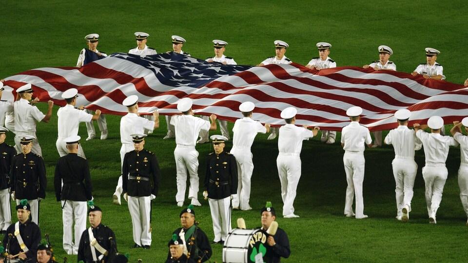 Un immense drapeau américain flotte au-dessus du terrain, tenu par des membres de la marine américaine.