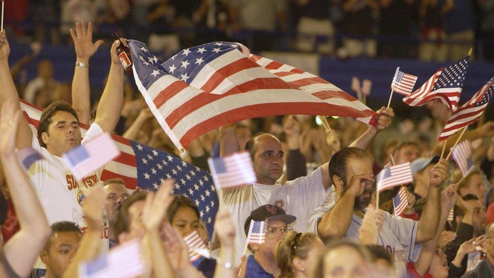 Des spectateurs émus brandissent des drapeaux américains.