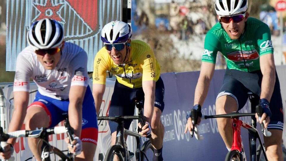Trois cyclistes pédalent.