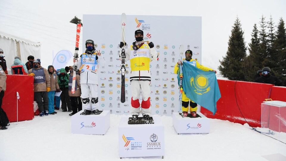 Trois skieurs sont sur un podium.