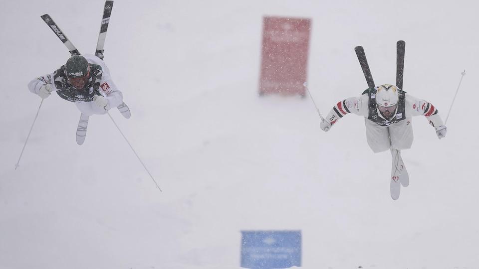 Mikaël Kingsbury et Benjamin Cavet effectuent un saut lors de la Coupe du monde de ski acrobatique, à Deer Valley, en Utah.