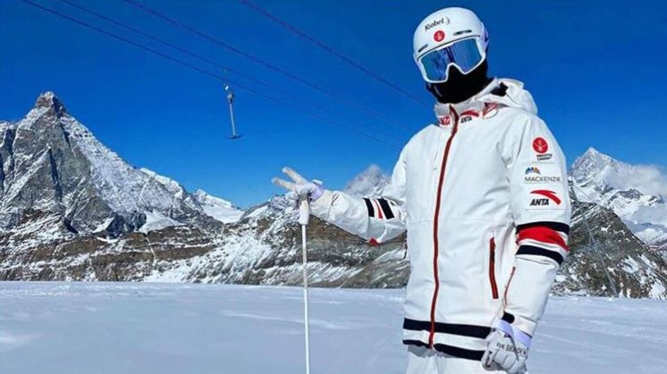 Un skieur acrobatique vêtu de blanc prend la pose sur une piste devant le mont Cervin en Suisse.