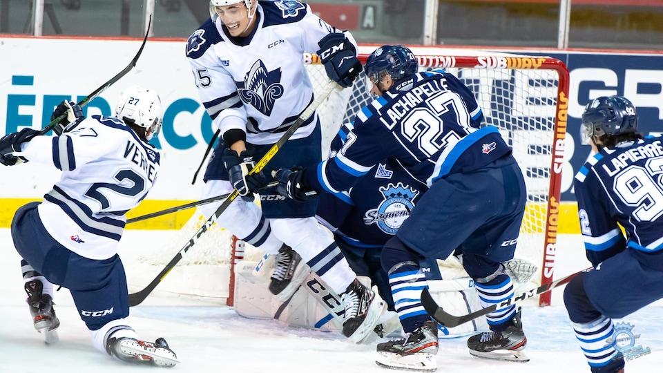 Un joueur de hockey saute dans les airs pour laisser passer la rondelle après le tir d'un coéquipier.