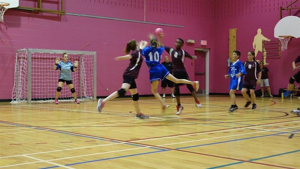 Des jeunes jouent. Une joueuse s'apprête à tirer le ballon en sautant.