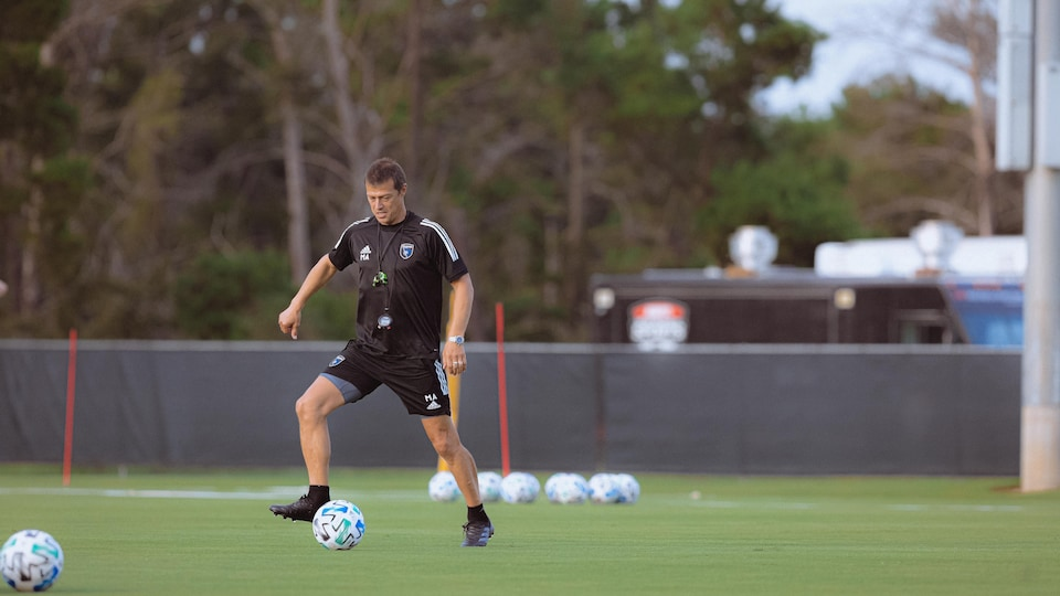 Il maîtrise un ballon du pied droit avant un entraînement.