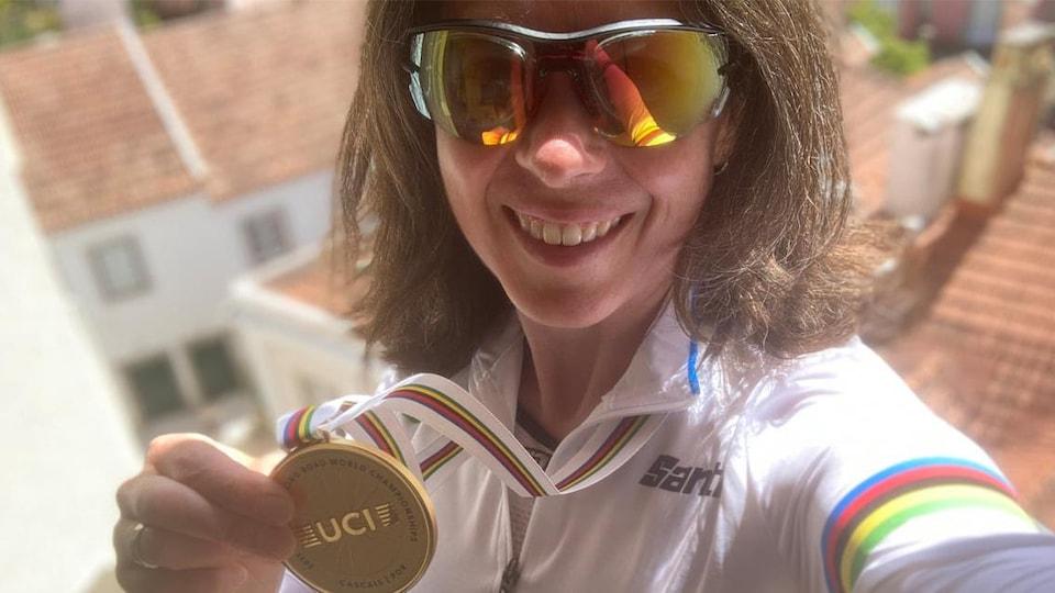 Une cycliste avec des lunettes de soleil sourit.