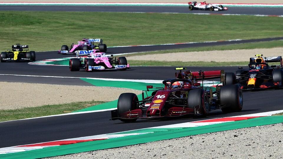 Charles Leclerc (Ferrari no 16) roule sur le circuit de Mugello dans sa voiture rouge devant une file de voitures.