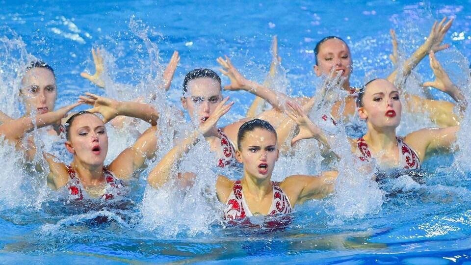 Les nageuses en action bras au-dessus de la tête, toutes en position identique.