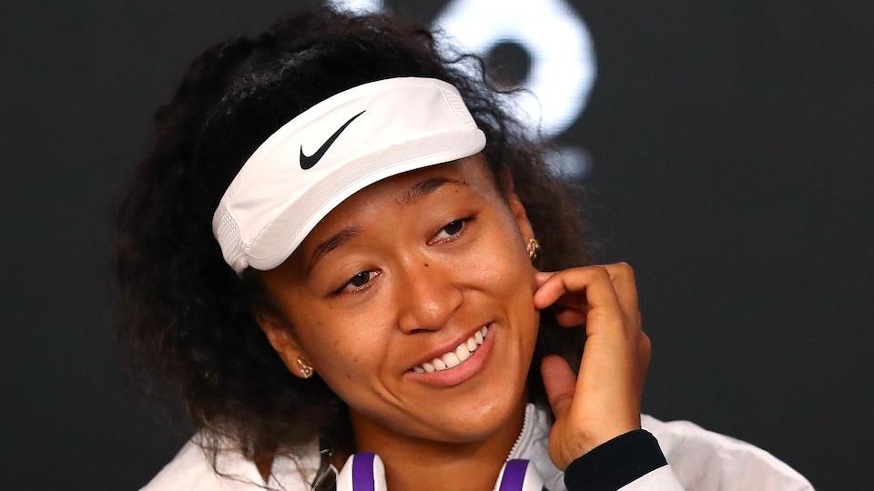 Elle sourit en conférence de presse.