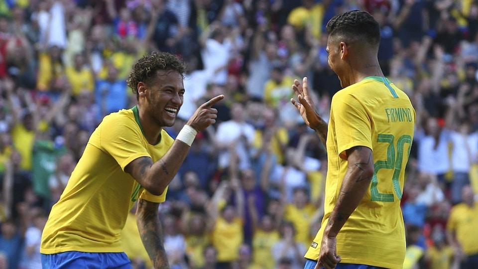 Les Brésiliens Neymar et Roberto Firmino sourient après avoir marqué un but en match amical contre la Croatie.