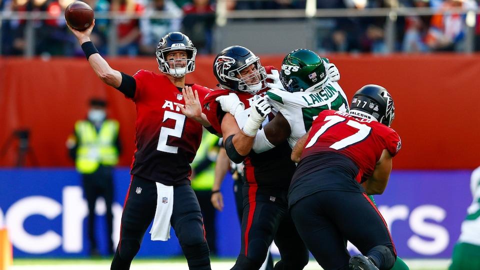 Un joueur de football américain lance un ballon.