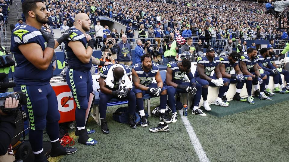 Les joueurs restent assis lors de l'hyme national américain avant la partie.