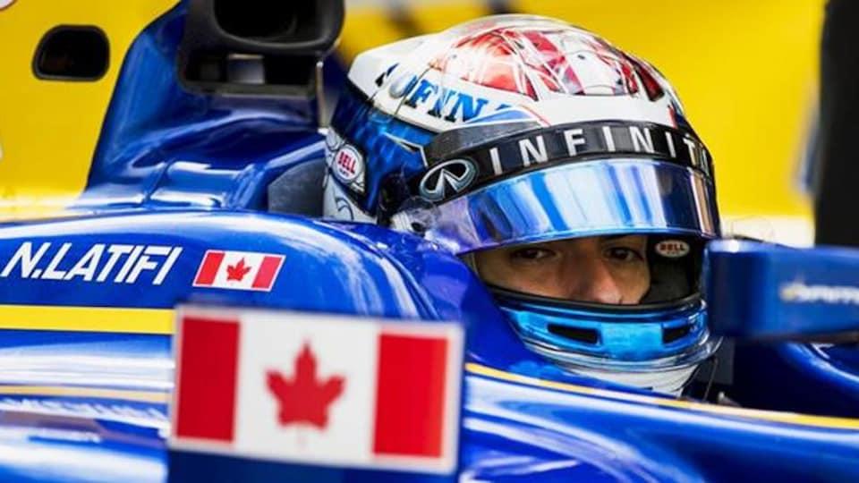 On voit le drapeau canadien et son nom sur la voiture.