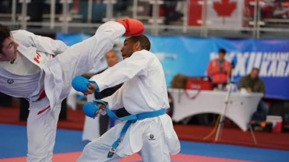 Un jeune homme frappe son adversaire de karaté à la tête pendant une compétition.