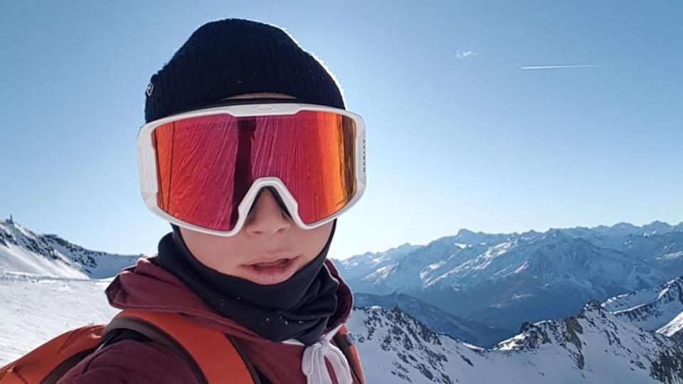 Il est au sommet d'une montagne avec un manteau rouge.