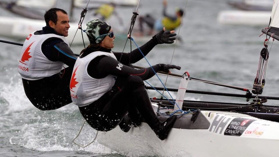 Un homme et une femme dirigent une embarcation.