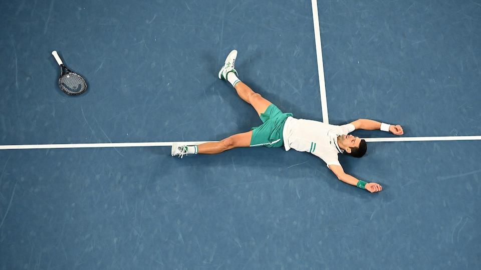 Il est couché sur le terrain bleu après son triomphe.
