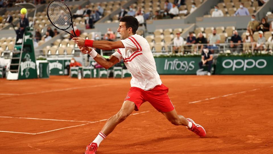 Le joueur serbe glisse sur la terre battue rouge pour frapper la balle du revers.