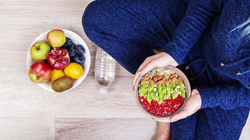 Une femme tient un bol de fruits et de noix