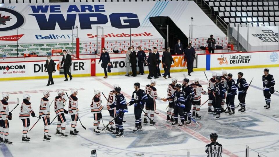 Les joueurs des Oilers et des Jets se donnent la main au centre de la patinoire.