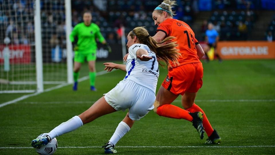 Deux joueuses luttent pour la possession du ballon près de la ligne de fond.