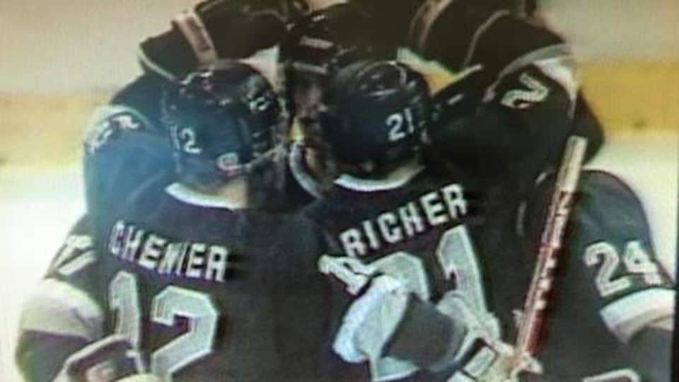 Des joueurs de hockey célèbrent un but sur la patinoire, ils portent un chandail noir et gris.