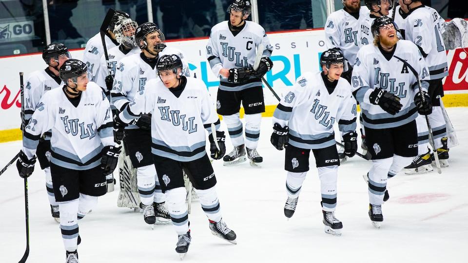 Des joueurs de hockey quittent la patinoire après un match.