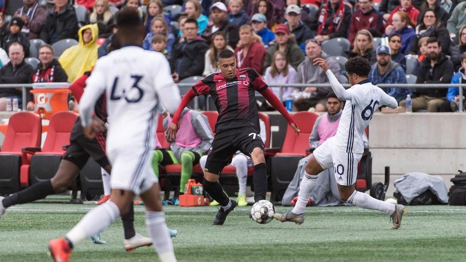 Un joueur de soccer tente de toucher le ballon du bout du pied pendant un match alors qu'un adversaire s'approche de lui