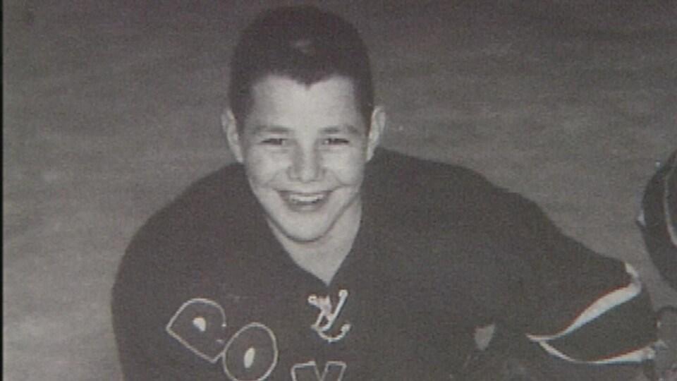 Jeune homme souriant. Photo en noir et blanc.