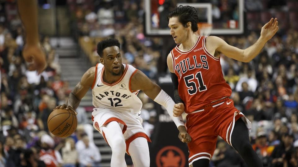 Un joueur de basketball se défait de la couverture d'un joueur adverse en dribblant le ballon lors d'un match de la NBA entre les Raptors de Toronto et les Bulls de Chicago.
