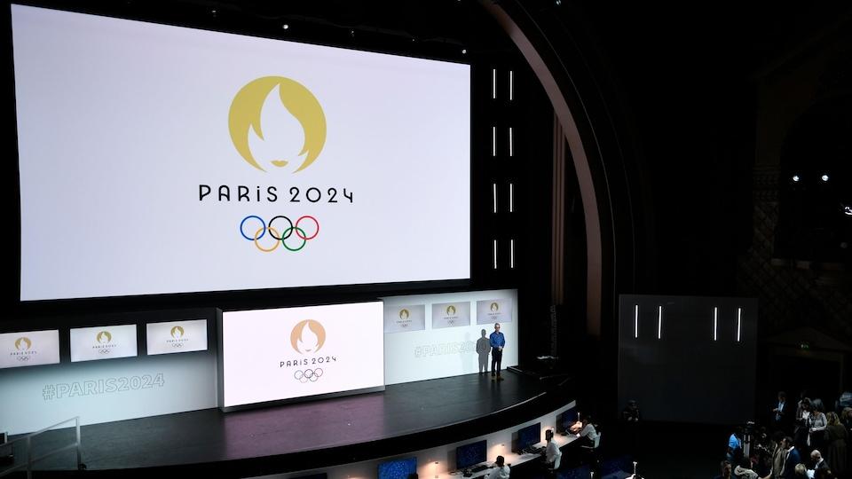 Le logo apparaît sur un écran blanc devant des gens rassemblés dans une salle.