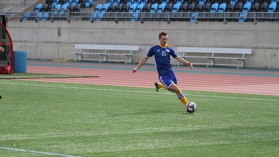 Pascal Doucette dans l'uniforme des Aigles Bleus de l'Université de Moncton botte un ballon.