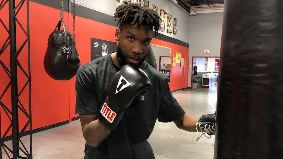 Un boxeur frappe sur un sac.