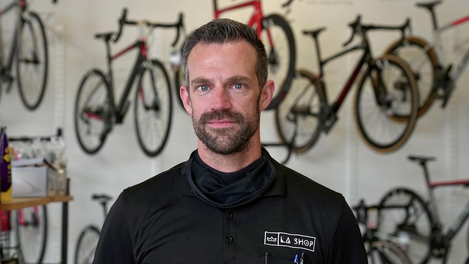 Un homme fixe la caméra devant des supports à vélo.