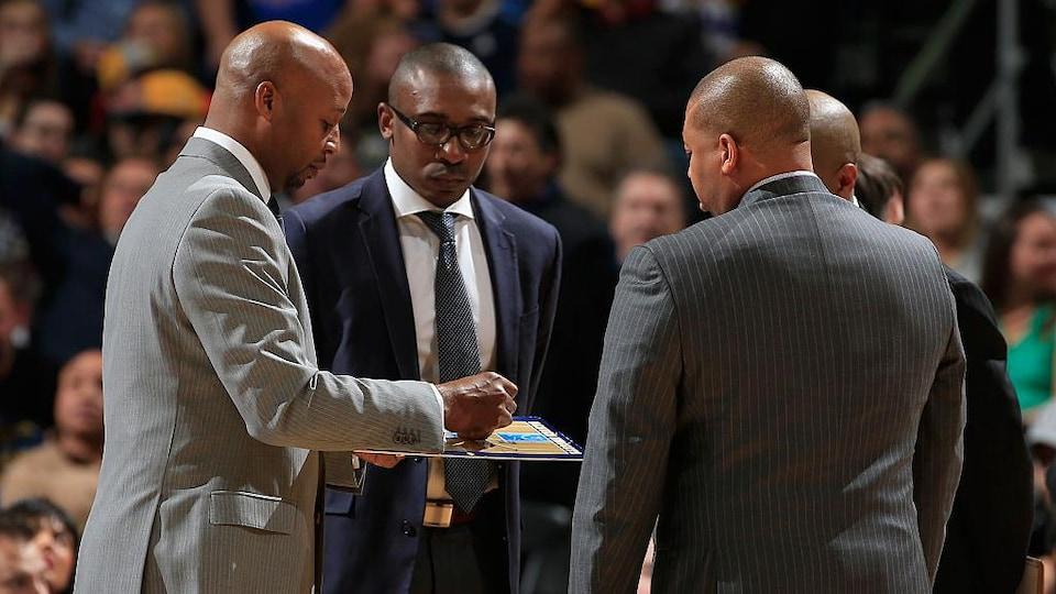 Patrick Mutombo s'entretient avec d'autres entraîneurs lors d'un temps d'arrêt.