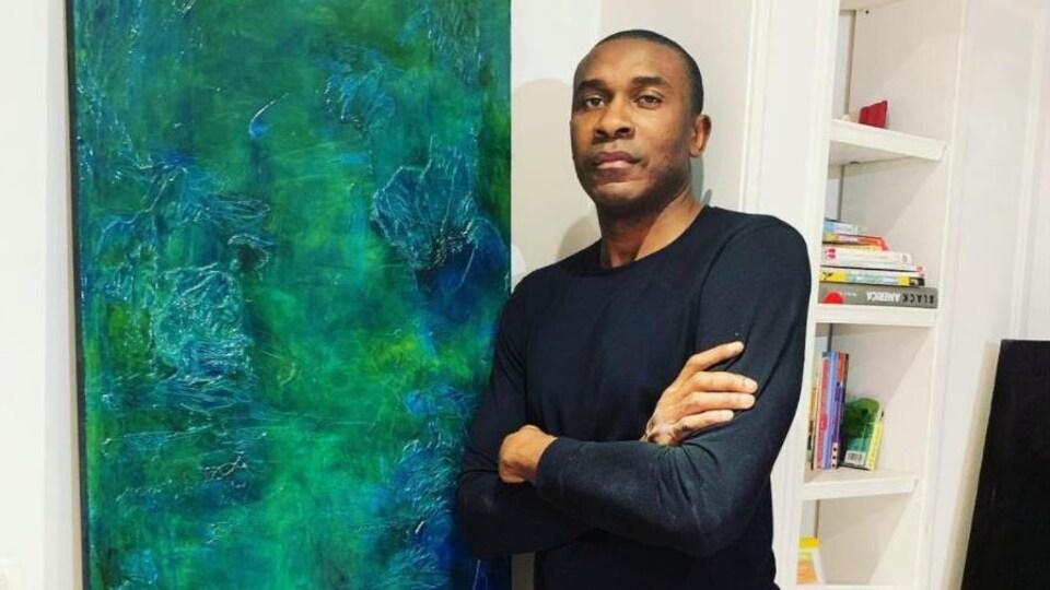 Patrick Mutombo pose aux côtés d'une de ses toiles.