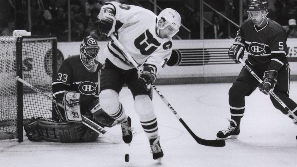 Patrick Roy, du Canadien de Montréal  observe attentivement la rondelle que tente de contrôler Ron Francis, des Whalers de Hartford, sous le regard du défenseur Rick Green, en 1989.
