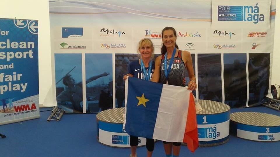 Patty Blanchard, à droite, et sa rivale Lesley Hinz, avec le drapeau acadien. Les deux dames ont leur médaille au cou.