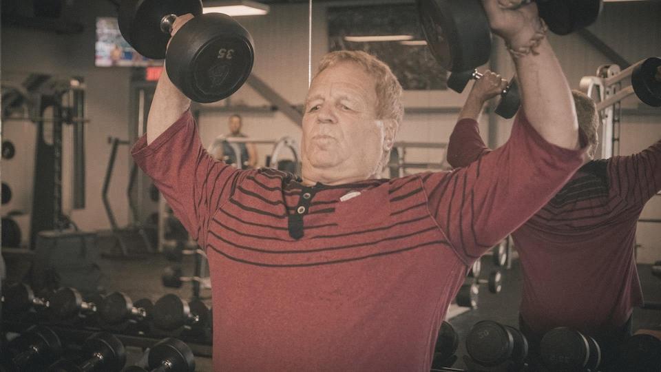 Un homme soulève des poids dans un gymnase